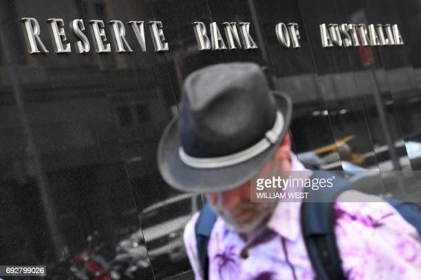 A man walks past the Reserve Bank of Australia sign in Sydney on June 6 2017 Australia's central bank held interest rates at a record low 150 percent...