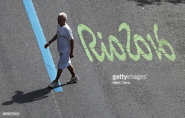 A man walks past the Rio2016 logo painted on a street in the Ipanema neighborhood on August 4 2016 in Rio de Janeiro Brazil The Rio 2016 Olympic...