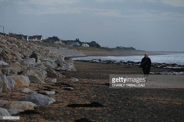 A man walks past the 'riprap' shoreline defence below a cliff where a landslide occured in 2008 on the Maritime Boulevard in BarnevilleCarteret...