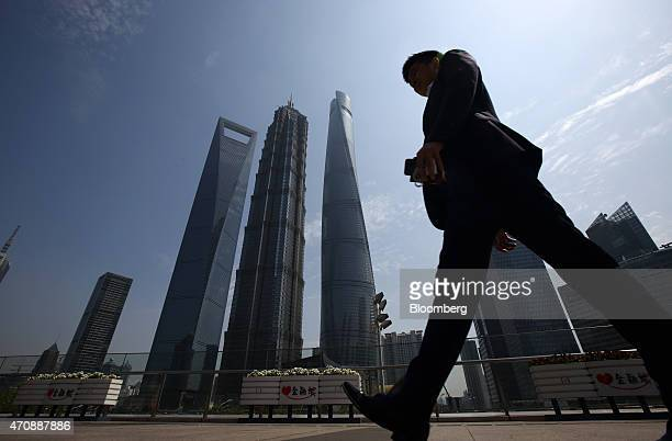 A man walks past the Shanghai World Financial Center second from left Jin Mao Tower third from left Shanghai Tower fourth from left and other...