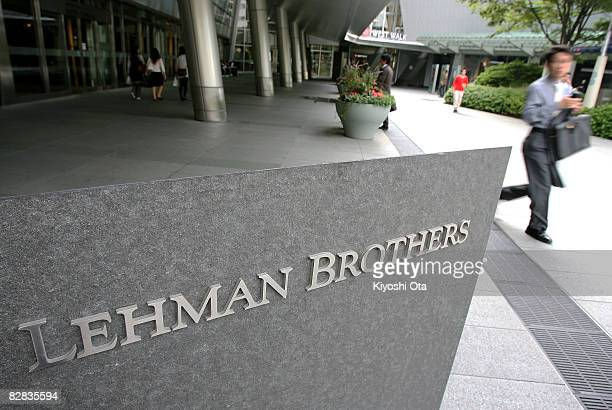 Man walks past the sign of Lehman Brothers Holdings at the Tokyo branch of Lehman Brothers Holdings on September 16, 2008 in Tokyo, Japan. The...