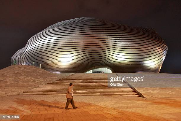 A man walks past the slick Ordos Museum during night in Kangbashi New District of Ordos City Inner Mongolia China on 92 July 2011 With an investment...