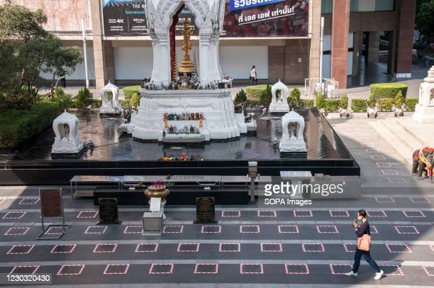 Man walks past the social distancing area in front of the shrine. The Thai government has applied social distancing measures for department stores...