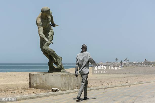 A man walks past the statue of a runner on the waterfront of Dakar on May 3 2016 / AFP / SEYLLOU