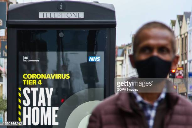 Man walks past the 'Stay Home' sign in London as many parts of the UK are now under 'Stay at Home' COVID-19 Tier 4 restrictions.