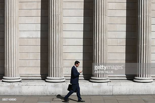 A man walks past the the Bank of England in central London on August 4 ahead of an expected interest rate reduction The Bank of England is expected...