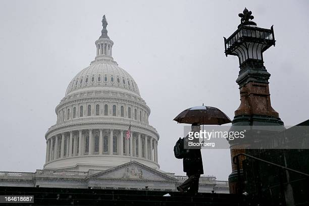 A man walks past the US Capitol holding an umbrella in Washington DC US on Monday March 25 2013 An early spring snowstorm tied up air traffic along...