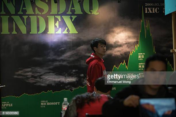 A man walks past the wall which print some companies listed on NASDAQ in '3W Cafe'on March 18 2016 in Beijing ChinaThe cafe serves as a hub for...