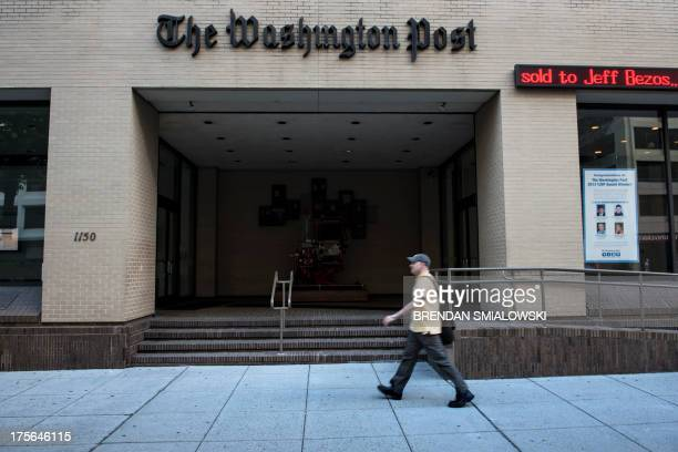 A man walks past The Washington Post building on August 5 2013 in Washington DC after it was announced that Amazoncom founder and CEO Jeff Bezos had...