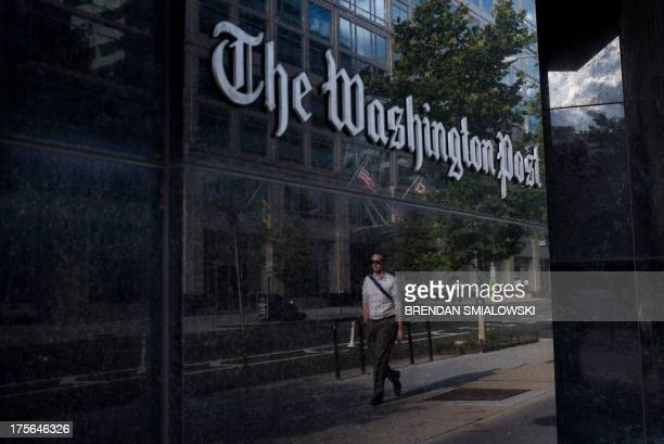 A man walks past The Washington Post on August 5 2013 in Washington DC after it was announced that Amazoncom founder and CEO Jeff Bezos had agreed to...
