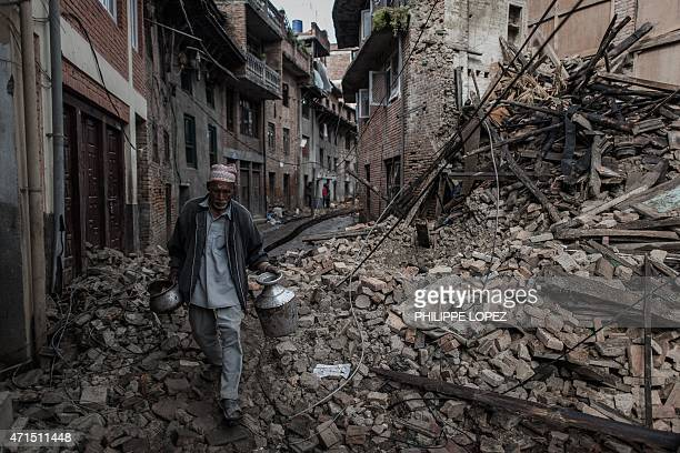 A man walks past the wreckage of a building in Khokana a village dating back hundreds of years on the outskirts of Kathmandu on April 29 following a...