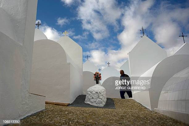 A man walks past tombstones in a cemetery in Casabermeja near to Malaga on November 1 2010 All Saints' Day is a solemnity celebrated in honour of all...