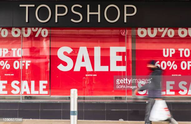 Man walks past TOPSHOP fashion store with Sales signs in Wales. The new, highly contagious strain of the virus has taken a firm foothold in Wales....