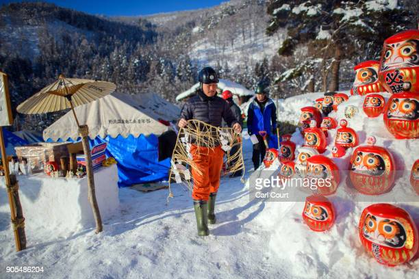 A man walks past traditional Japanese Daruma dolls placed in the snow as villagers work on building a shrine during preparations for the Nozawaonsen...