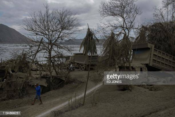 TOPSHOT A man walks past trees and and a truck covered in ash from the eruption of Taal volcano in Buso Buso on January 20 2020 Philippine...