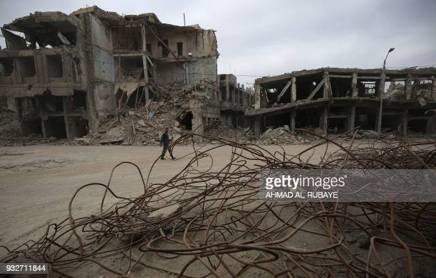 TOPSHOT A man walks past twisted metal in a residental in the Old City of Mosul on March 15 2018 eight months after Iraqi forces liberated the city...