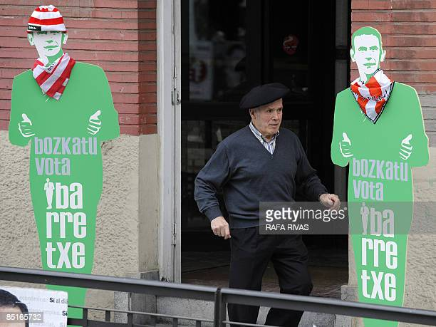 A man walks past two cutout figures wearing Athletic de Bilbao football team's scarves of the current Basque regional president and Basque...