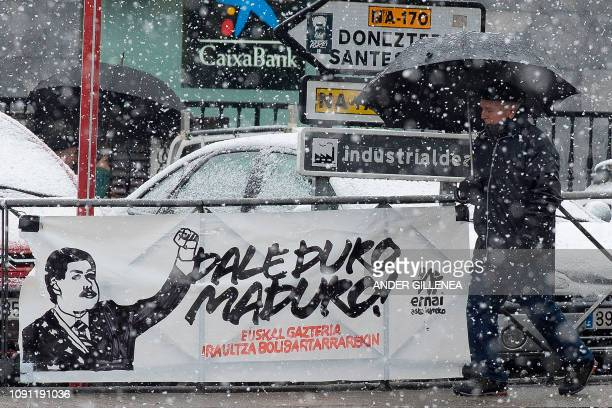 A man walks past under the snow a banner reading 'Be hard Maduro the Basque youth is with the Bolivarian revolution' in support of Venezuelan...