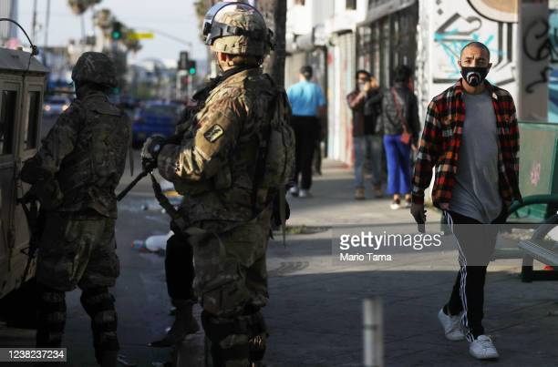 Man walks past U.S. National Guard troops in the Fairfax District, an area damaged during yesterday's unrest, after being activated by California...