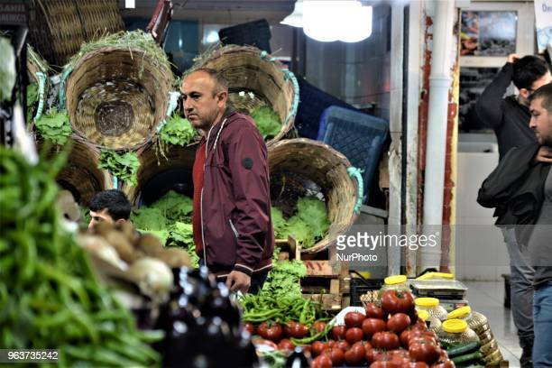 A man walks past vegetables sitting on a counter in a bazaar during the Muslim holy fasting month of Ramadan in the historic Ulus district of Ankara...