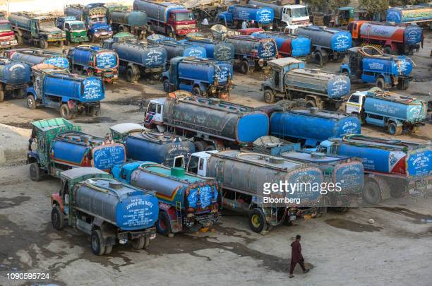 A man walks past water tankers sitting parked in Karachi Pakistan on Monday Dec 24 2018 Women and children walk miles each day in search forwaterin...
