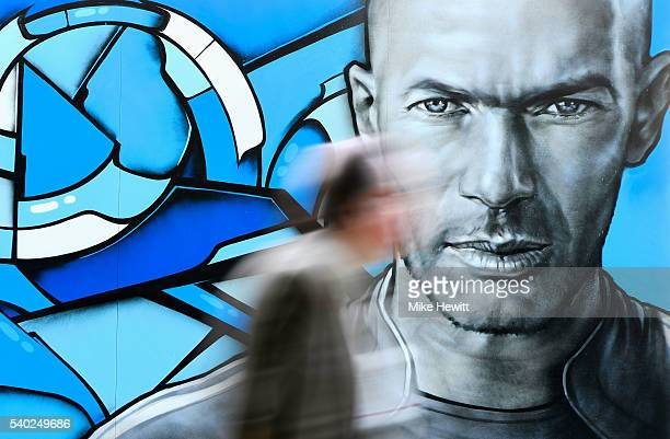 A man walks past Zinedine Zidane graffiti ahead of the UEFA Euro 2016 near Hotel de Ville on June 9 2016 in Paris France The opening match of the...