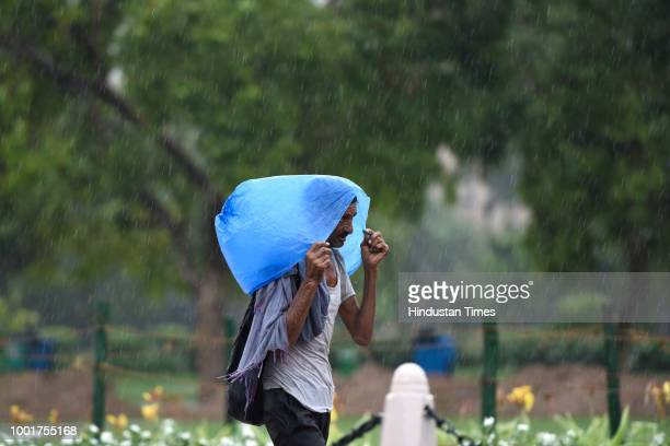 Man walks taking cover under polythene bag to protect himself from rains near India Gate on July 13, 2018 in New Delhi, India. The national capital...