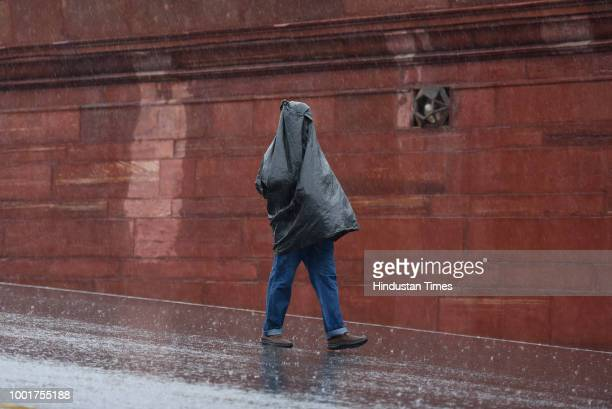 Man walks taking cover under trash bag to protect himself from rains near North Block on July 13, 2018 in New Delhi, India. The national capital...