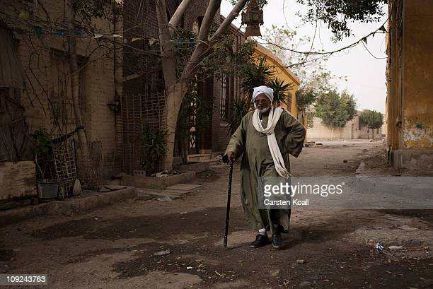 A man walks the way in front of the entrance of a mausoleum at the Al Qarafa Cemetery on Feburary 15 2011 in Cairo Egypt Over 6000 people live and...