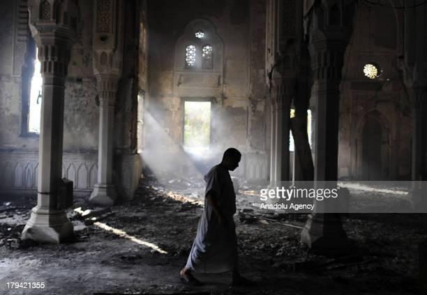 A man walks thorough the burnt out Raba'a alAdawiya Mosque on August 15 2013 in Raba'a alAdawiya Square in CairoEgypt The Raba'a alAdawiya mosque...