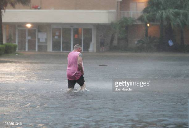 Man walks though a flooded parking lot as the outer bands of Hurricane Sally come ashore on September 15, 2020 in Gulf Shores, Alabama. The storm is...