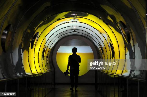 A man walks through a channel as he visits a beer museum in Qingdao east China Shandong province on July 24 2014 A key measure of Chinese...