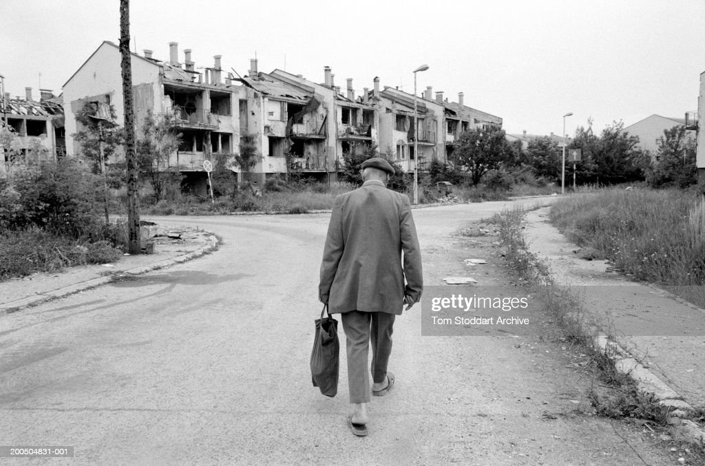 Bosnia, Sarajevo - September 1995. A man walks through a deserted street towards his house in a heavily bomb damaged area near Sarajevo airport. During the 47 months between the spring of 1992 and February 1996, the people of Sarajevo endured the longest siege Europe has witnessed since the end of the Second World War. More than 10,600 people were killed with a further 56,000 wounded or maimed.