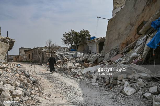 Man walks through a destroyed neighbourhood in the village of al-Mastuma, about 7 kilometres south of Idlib city in northwestern Syria, on March 10,...