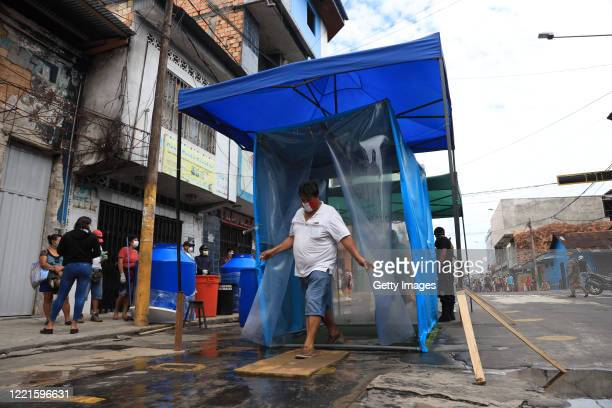 Man walks through a disinfection tunnel before entering the Belen Market at Belen market during COVID-19 pandemic on April 27, 2020 in Belén, Peru....