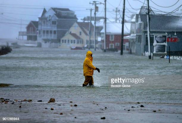 A man walks through a flooded section of Brant Rock in Marshfield Mass on Jan 4 as the afternoon high tide struck during the blizzard