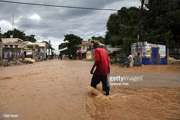 A man walks through a flooded street flooded due to Hurricane Tomas November 5 2010 in Leogane Haiti The storm which caused some flooding and heavy...