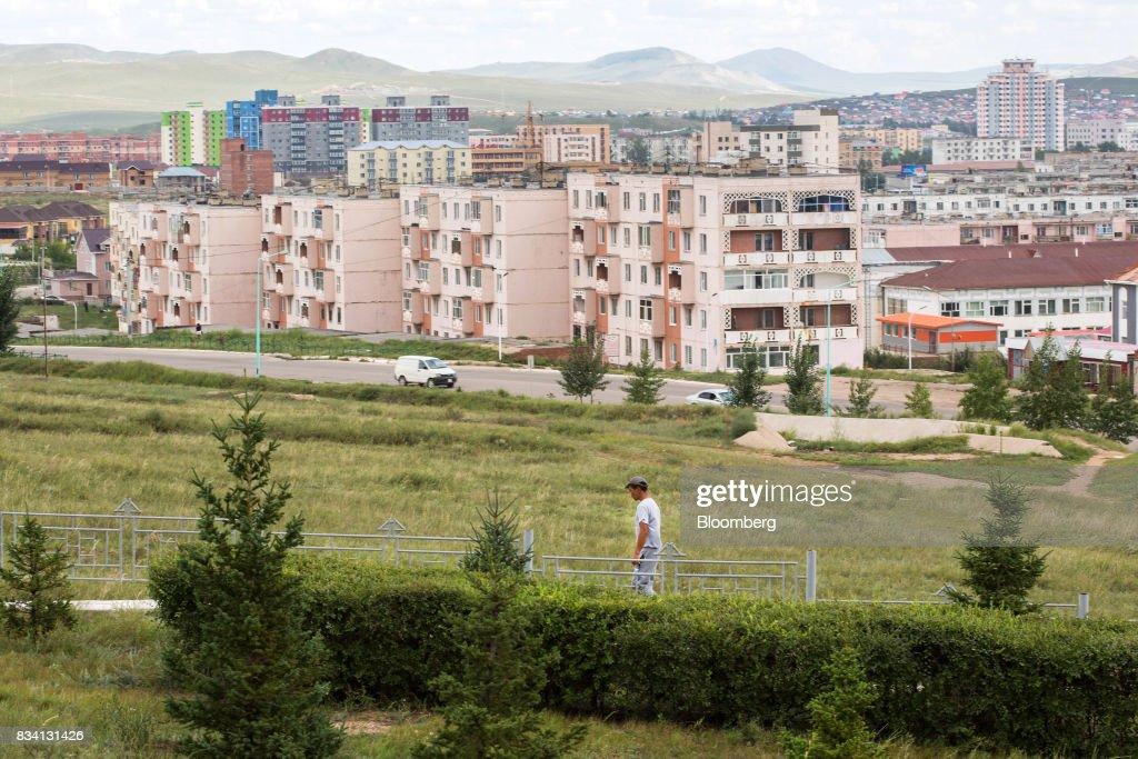 A man walks through a park as housing stands in the background in Darkhan, Mongolia, on Monday, Aug. 14, 2017. Mongolia, desperate to make more of its abundant resources as it seeks to revive its flailing economy, aims to make that vision a reality through one of the world's most ambitious power projects. The landlocked nation is considering a $7 billion plan to build coal, wind and solar plants that could send electricity across China, Russia, South Korea and Japan, according to the Shivee Energy Complex. Photograph: Taylor Weidman/Bloomberg via Getty Images