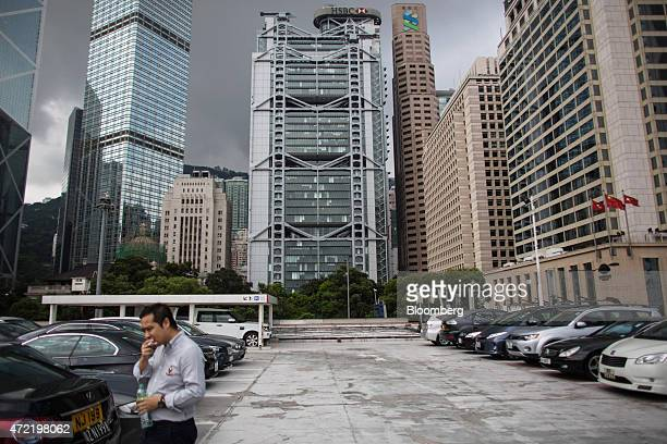 A man walks through a parking lot near the Bank of China Tower from left Cheung Kong Center Bank of China Building HSBC Holdings Plc headquarters...