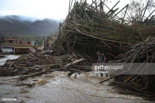 A man walks through a road that has been turned into a river caused by heavy rains after Hurricane Maria passed through on October 6 2017 in Utuado...