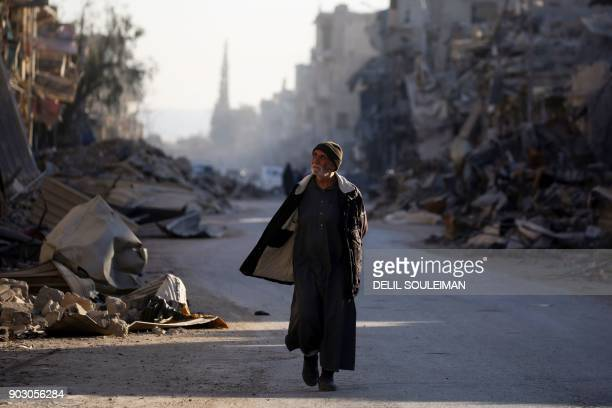 TOPSHOT A man walks through a street in Syria's devastated city of Raqa on January 9 2018 / AFP PHOTO / DELIL SOULEIMAN