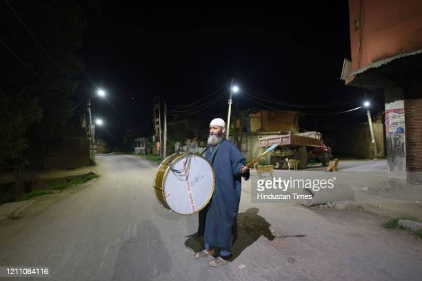 A man walks through a street while playing a drum and making calls for people to wake up for the predawn 'sehri' meal on the first day Ramzan on...