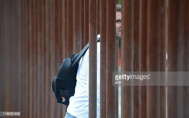 A man walks through a wall made of metallic poles separating east from west Berlin at the Bernauer strasse Wall memorial June 14 2011 Berlin marks...