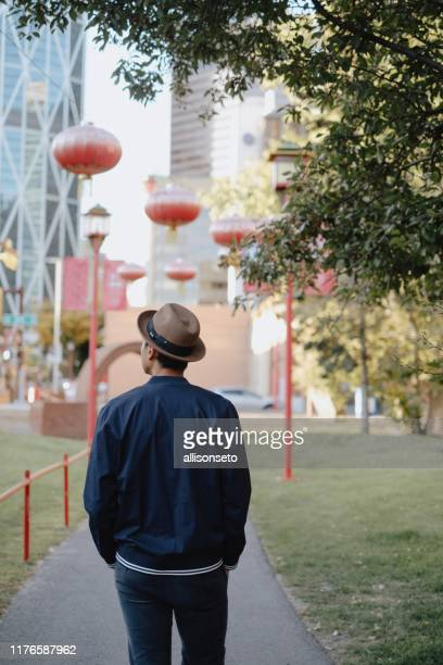 man walks through calgary chinatown - chinatown stock pictures, royalty-free photos & images