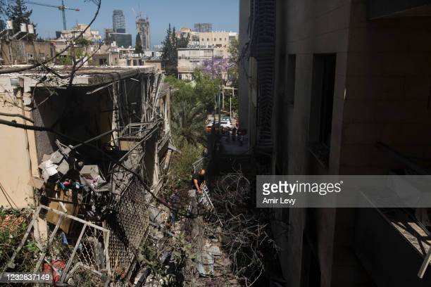 Man walks through debris after a rocket launched from the Gaza strip struck on May 12, 2021 in Giv'atayim, Israel. At least three dozen Palestinians...