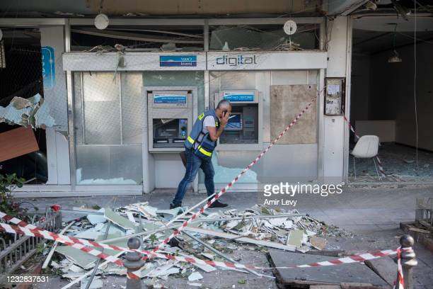 Man walks through debris after a rocket launched from the Gaza strip struck on May 12, 2021 in Holon, Israel. At least three dozen Palestinians and...