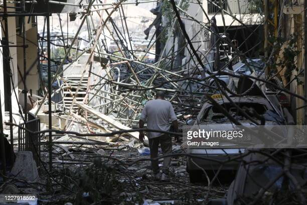 Man walks through debris on a residential street, devastated by an explosion a day earlier, on August 5, 2020 in Beirut, Lebanon. As of Wednesday...