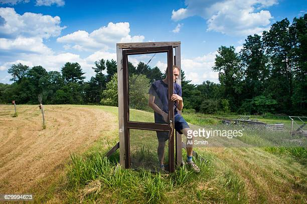 Man walks through door in field
