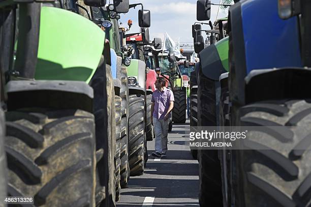 A man walks through farmers' tractors staging a national demonstration on September 3 2015 near Place de la Nation in Paris to protest against the...