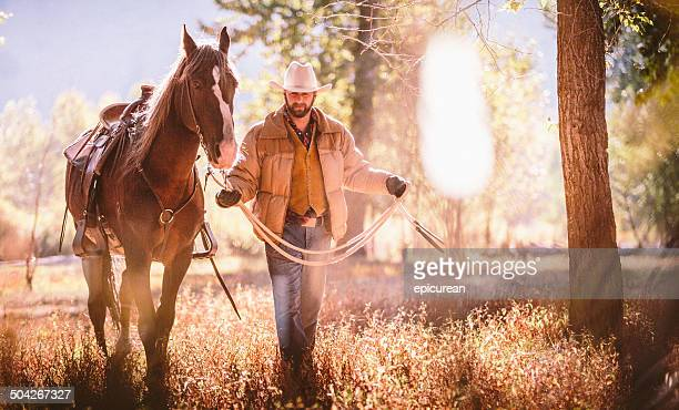 Man walks through field surrounded by trees while guiding horse